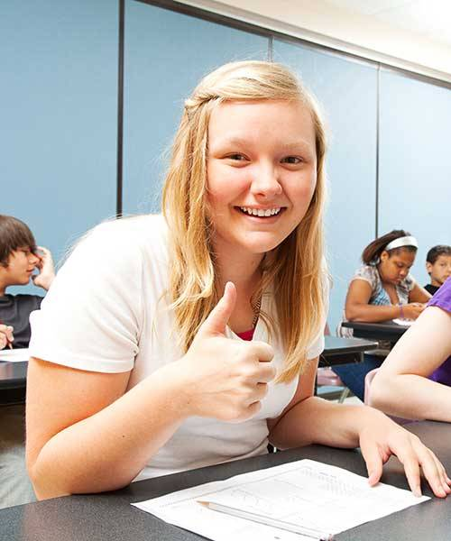 An online middle school student showing a thumbs up